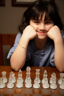 young girl with chess set